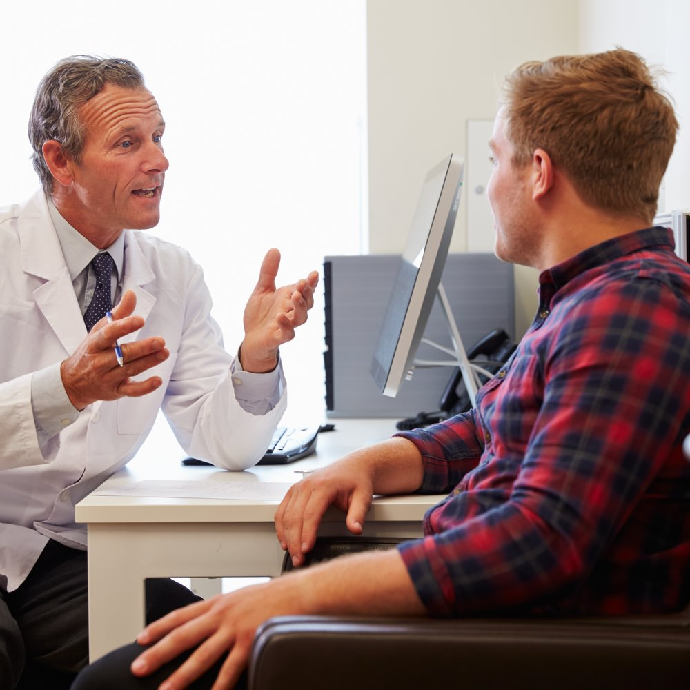 Patient Having Consultation With Male Doctor In Office
