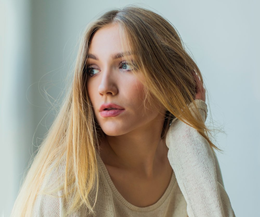 Young blonde woman sitting next to window in sweater, looking emotive and thoughtful
