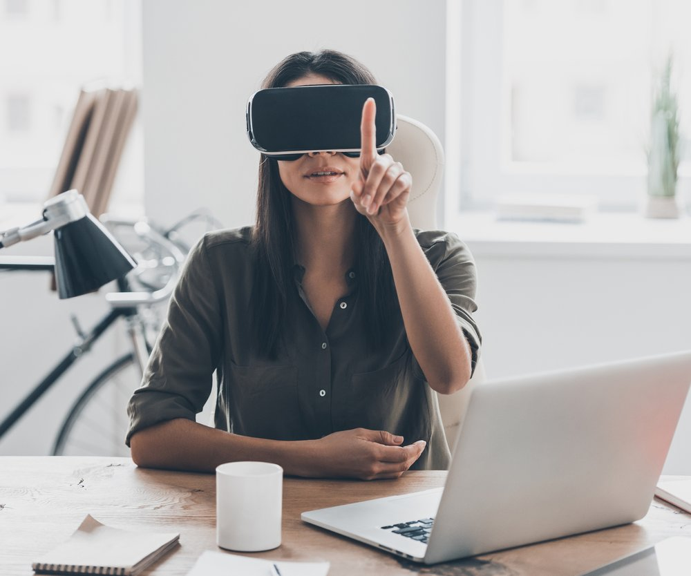Confident young woman in virtual reality headset pointing in the air while sitting at her working place in office