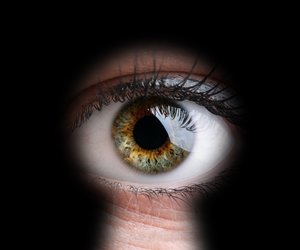 Womans eye peeking through a keyhole concept for curiosity, stalker, surveillance and security