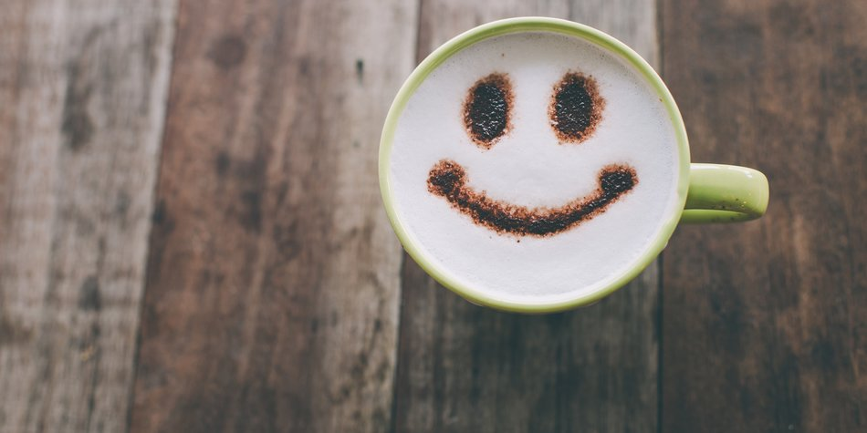 Happy face on coffee cup on wooden background with vintage colour effect. Still life.