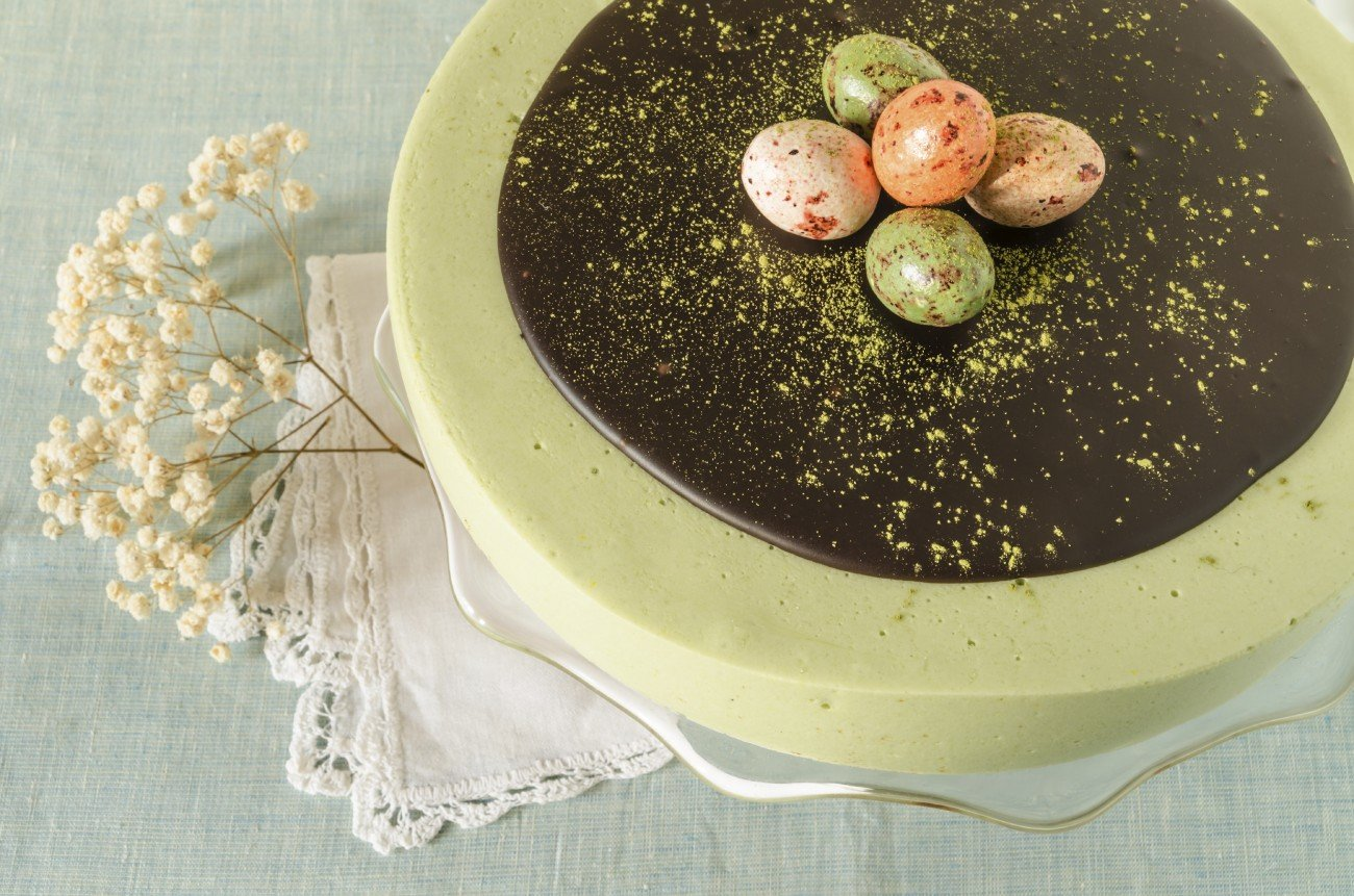 Easter cake with tea matcha decorated chocolate ganache and sweet-stuff eggs. Near cup of coffee. From series elegant desserts