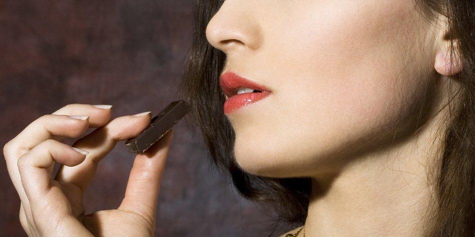 Eine Frau hält ein Stück Schokolade fest