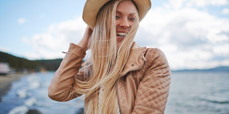 Frau steht am Meer, ihre Haare wehen im Wind, sie hält ihren Hut fest