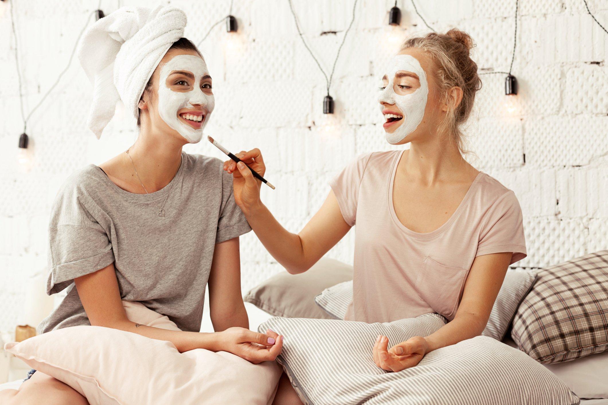 Frauen tragen sich gegenseitig Gesichtsmasken auf