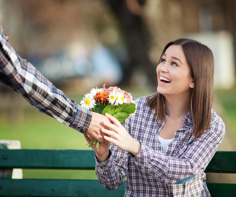 Mann überreicht Frau einen Blumenstrauß
