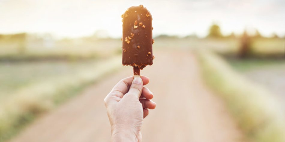 Hand of woman holding a chocolate popsicle on nature background