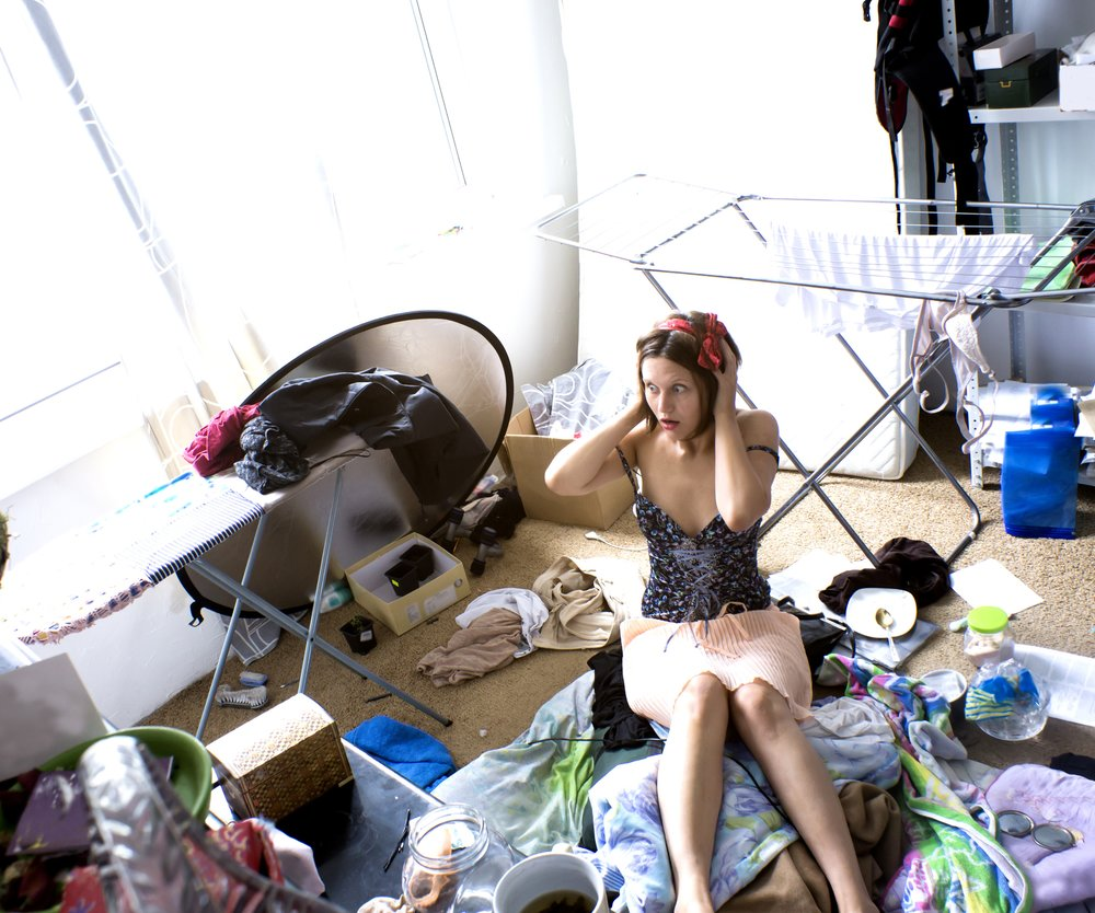 beautiful woman is expressing panic in her really messy room