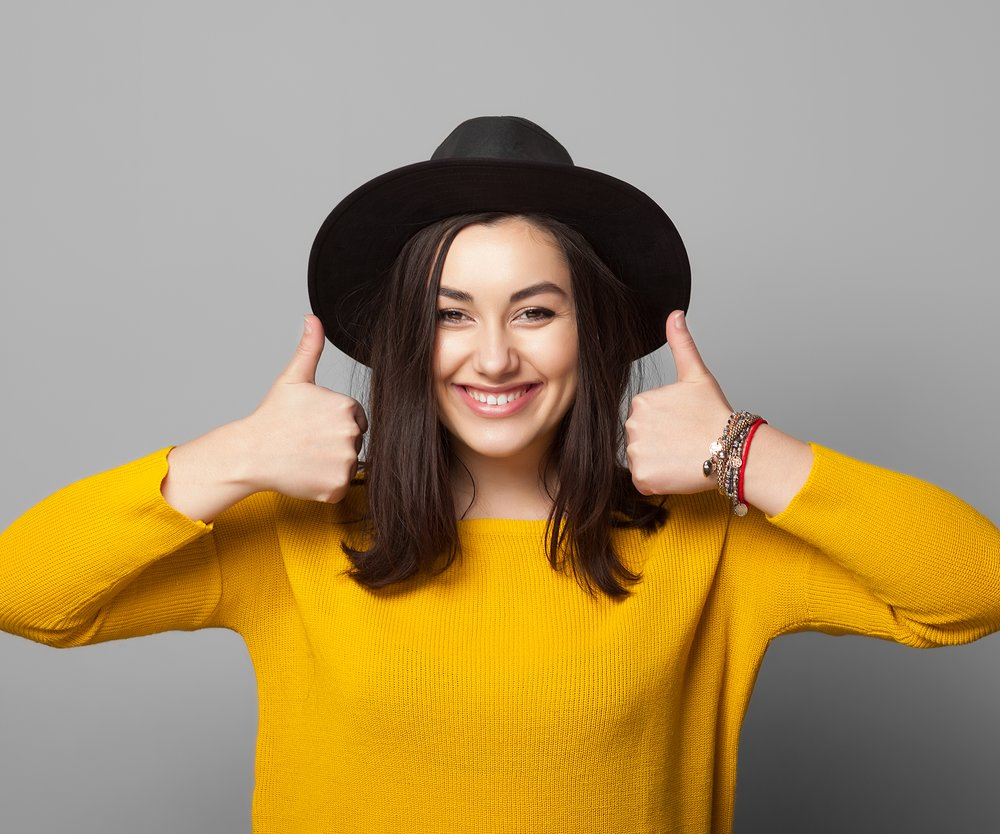 Portrait of trendy young woman showing thumb up over grey background