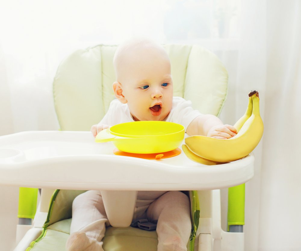 Baby sitting at the table home and takes fruits bananas