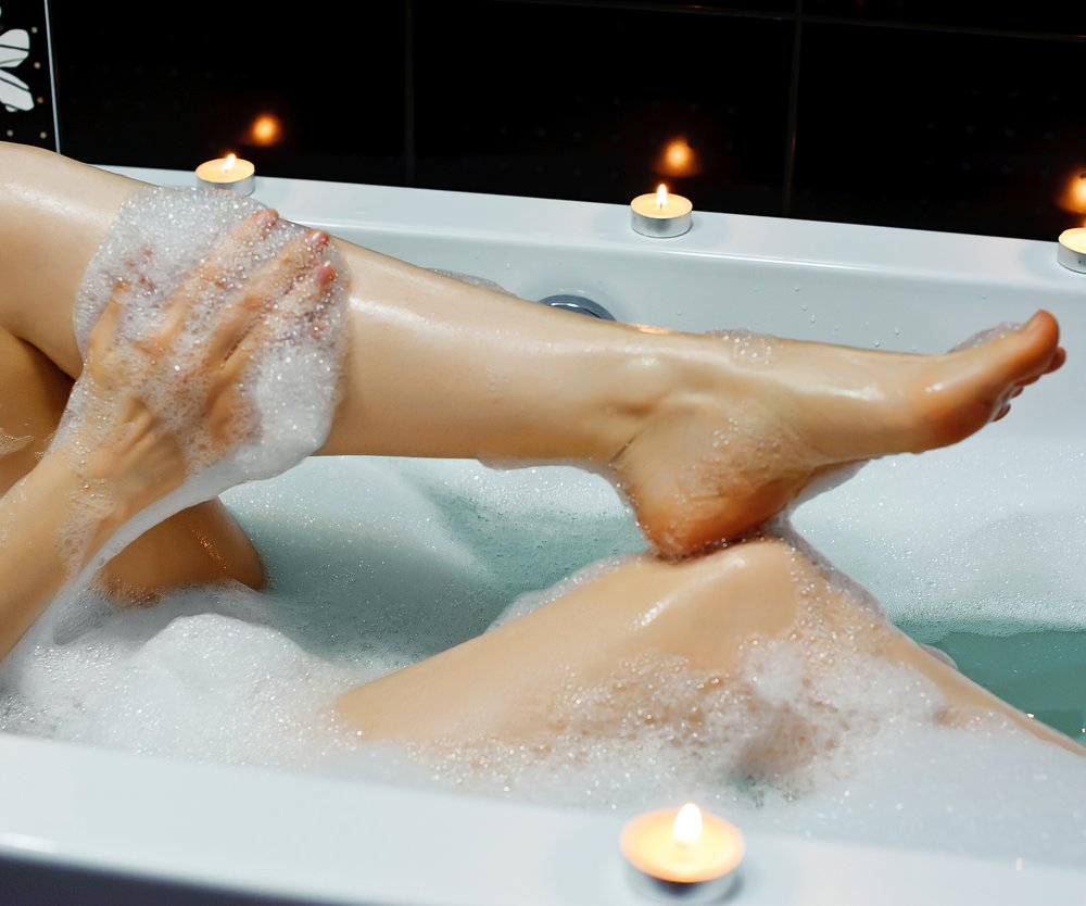 Woman taking bath. Legs.