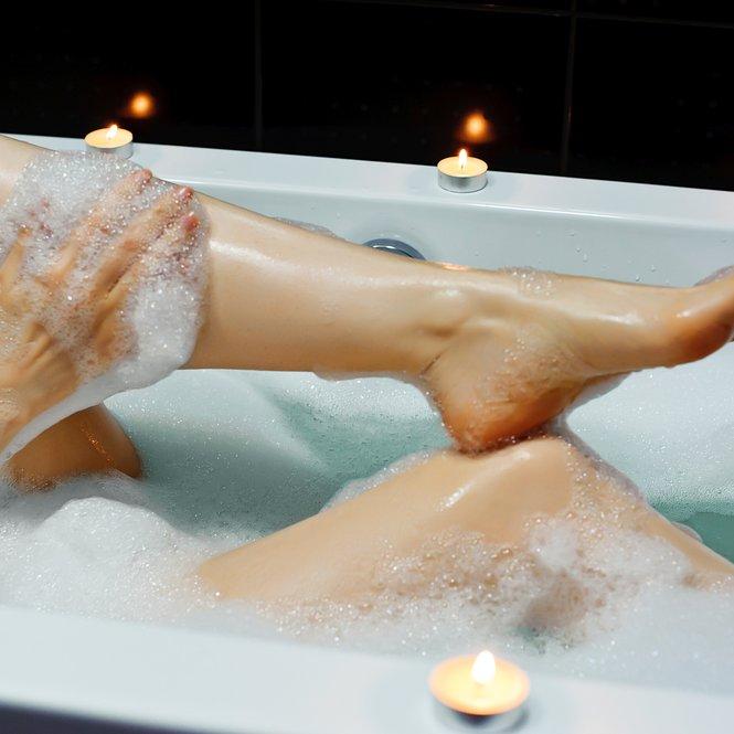 Woman taking bath. Legs.