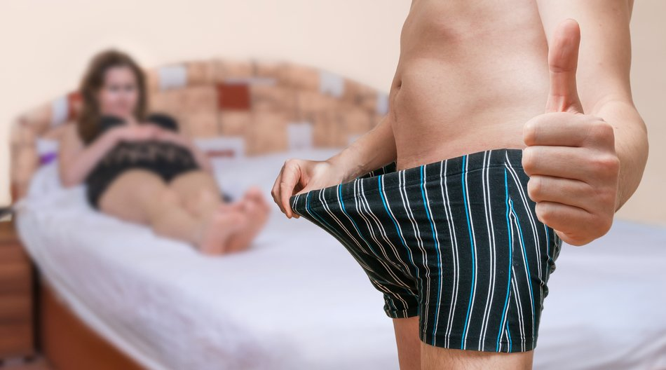 Impotence concept. Woman is waiting in bed on her lover who is looking on his penis after anti-impotence pill and shows thumb up that he is ready for sex.