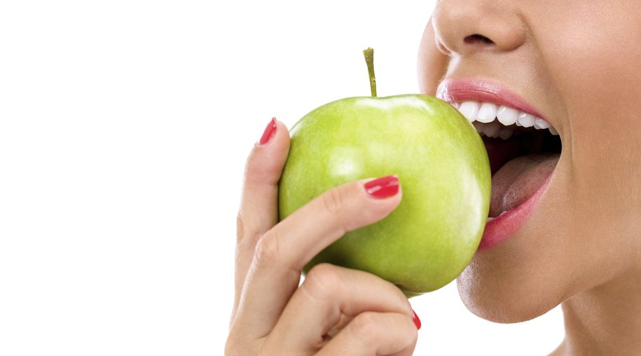 woman biting a green apple isolated on white