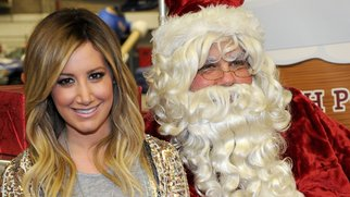 "NEW YORK, NY - DECEMBER 04: Ashley Tisdale (L) and Santa Claus join Delta Air Lines and YMCA Of Greater New York at ""Holiday Flight to The North Pole"" event for PS 197 elementary school students at JFK on December 4, 2013 in New York City. (Photo by Bryan Bedder/Getty Images)"