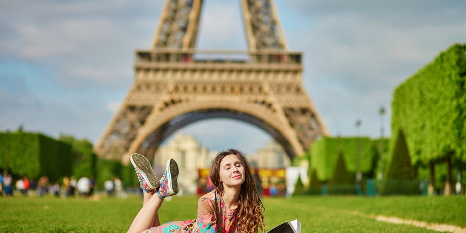 Beautiful woman in Paris lying on the grass near the Eiffel tower on a nice spring or summer day and reading a book. Student or schoolgirl doing her homework or preparing to exams