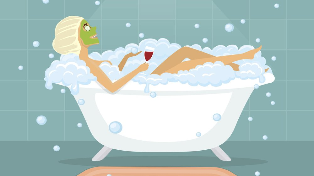 Woman taking a bubble bath in a vintage bathtub, relaxing, drinking wine, making facial mask
