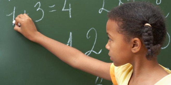 4. Klasse: Mädchen löst Rechenaufgabe an der Tafel