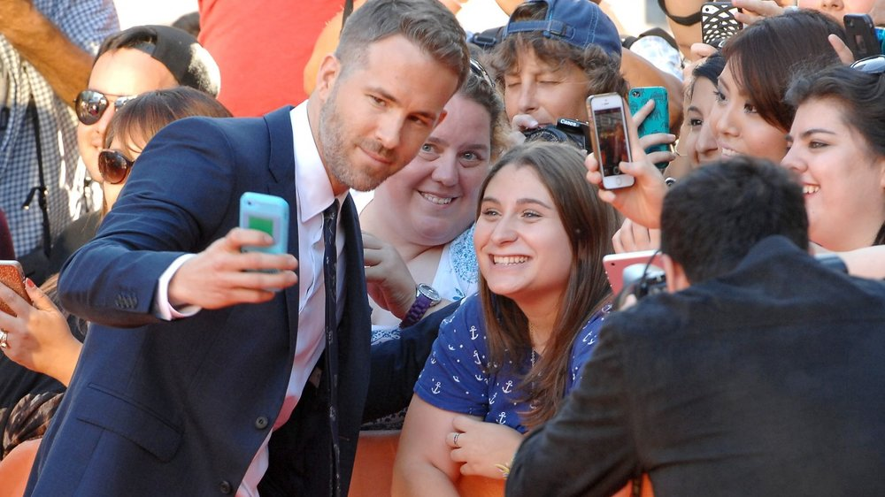 """TORONTO, ON - SEPTEMBER 16: Actor Ryan Reynolds takes a selfie with a fan during the """"Mississippi Grind"""" premiere during the 2015 Toronto International Film Festival at Roy Thomson Hall on September 16, 2015 in Toronto, Canada. (Photo by Sonia Recchia/Getty Images)"""