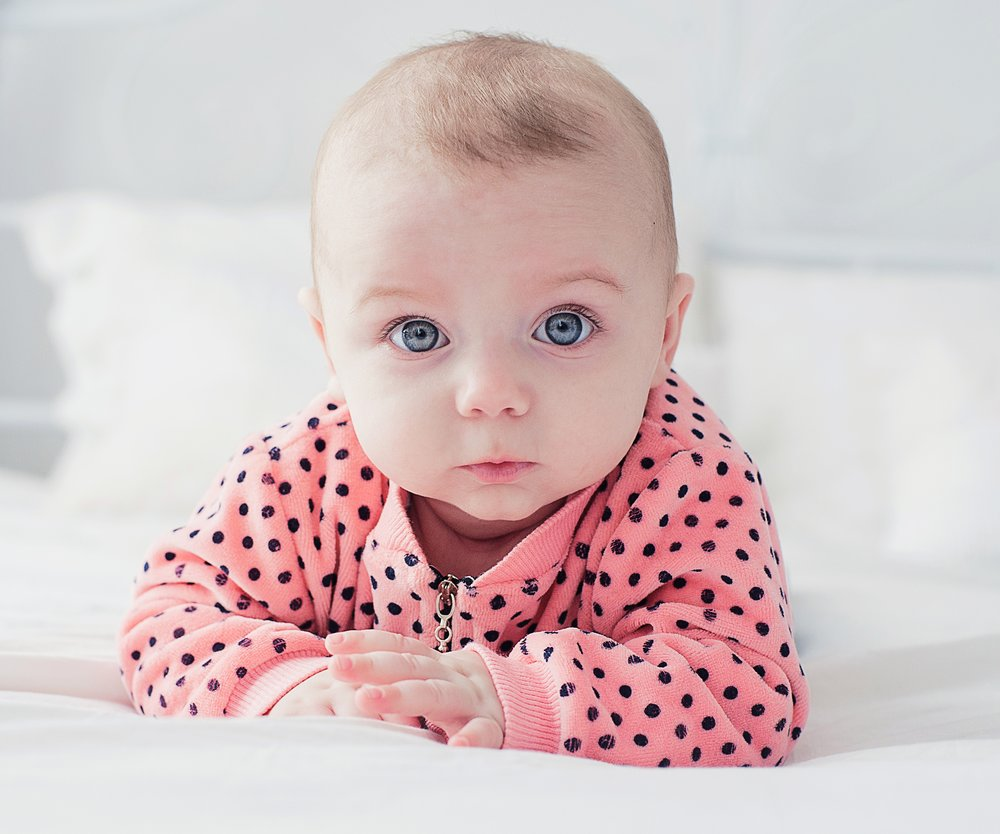 Cute baby girl on the white bed