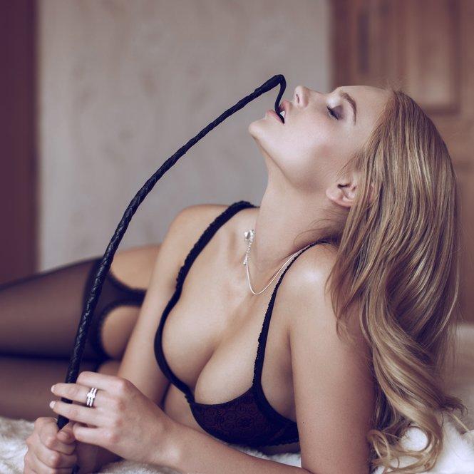 Frau mit Peitsche im Bett
