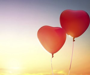 two red balloons in shape of heart on the background of sunset sky. the concept of love and Valentine's day.