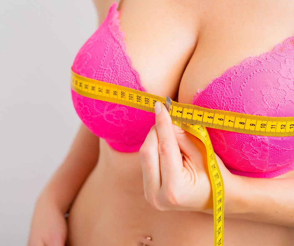 Close-up photo of female measuring her breasts with measurement tape