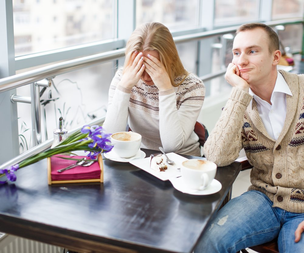 after a quarrel. girl sitting at a table covering his face with his hands, sad man looks away.