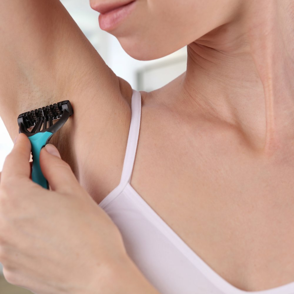 Attractive young woman using razor to remove hair from her armpit