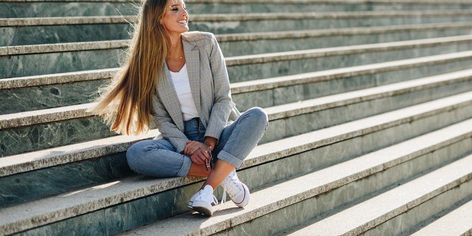 Frau sitzt auf einer Treppe in der Sonne