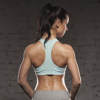 the back of sports women on training, fitness girl with muscular body, do her workout