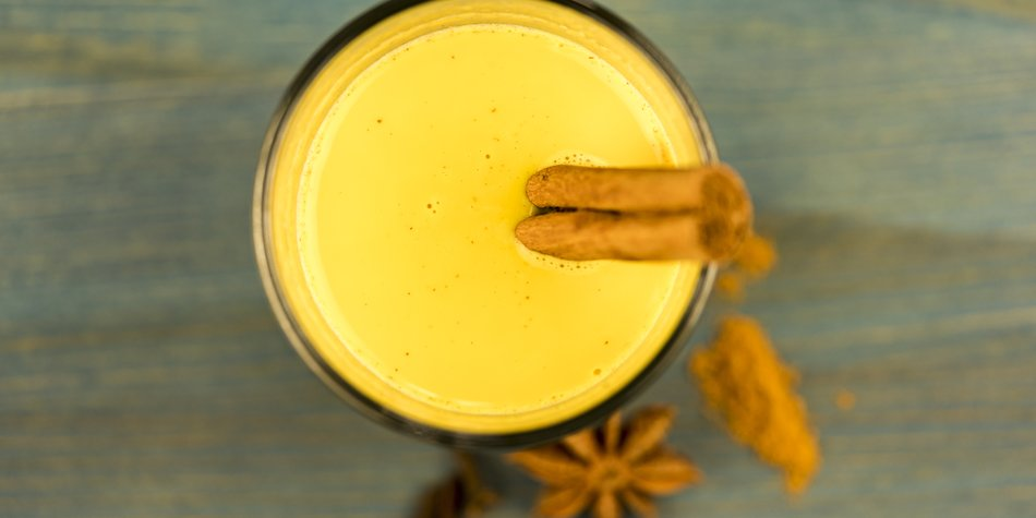 First person perspective top down view on curcuma latte with cinnamon sticks and anise herb on wooden table