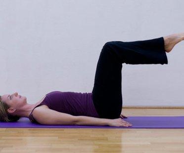 Schritt 1 der Pilatesübung Single Leg Stretch, bei der die Pilateslehrerin auf dem Rücken liegt