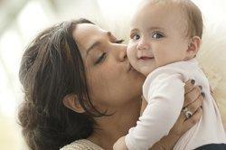 Baby, 6 Monate, wird geküsst.
