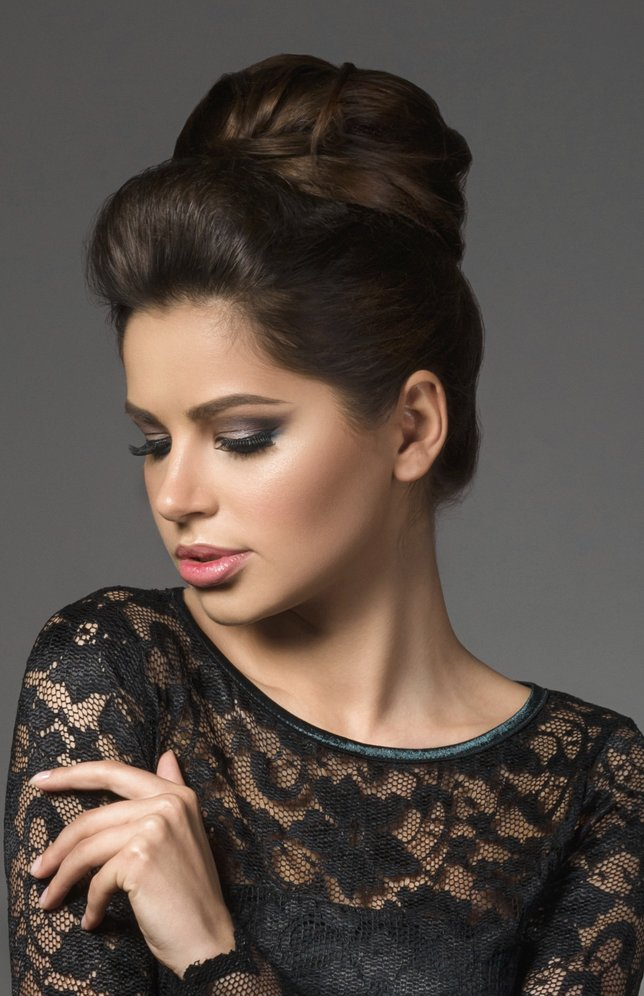 Beautiful young model in black dress with evening makeup and hairdo posing over gray background