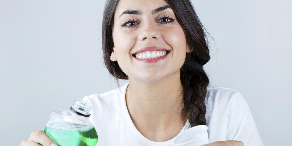Portrait of beautiful girl using mouthwash. Isolated on white.