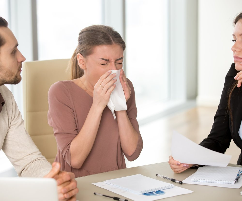 Sick young attractive woman with handkerchief has sneezing attack, blowing nose while working with colleagues on meeting, caught cold, flu symptom, weakened immune system due to stress or overwork