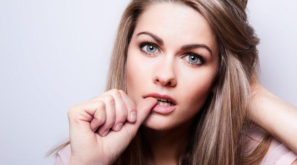 Frau kaut an ihren Nägeln