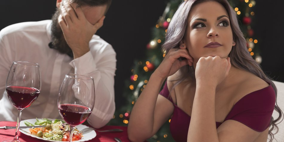 Beautiful young couple sitting at a table, having a fight over a romantic Christmas dinner