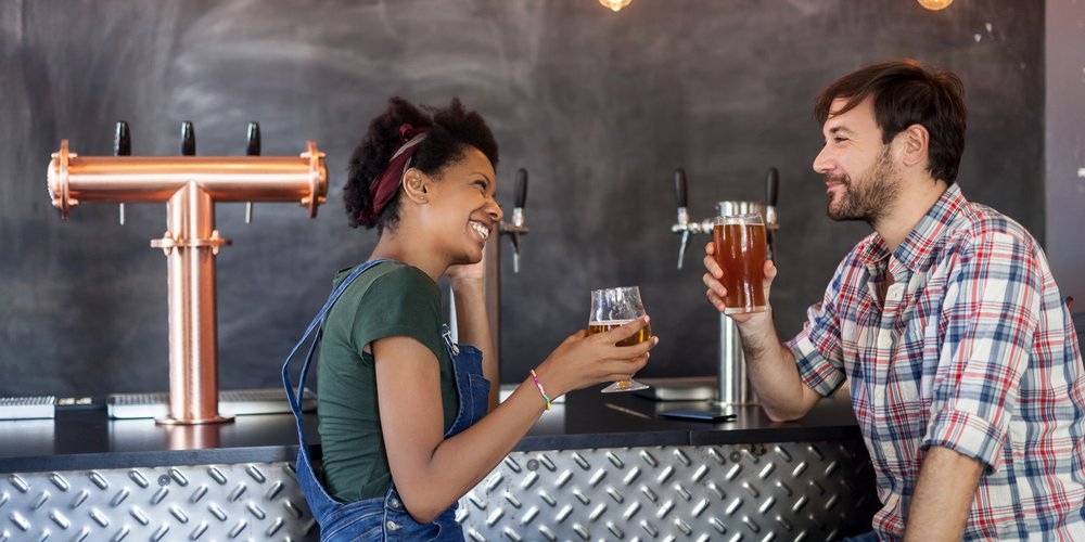 Multi-ethnic couple laughing in a beer bar