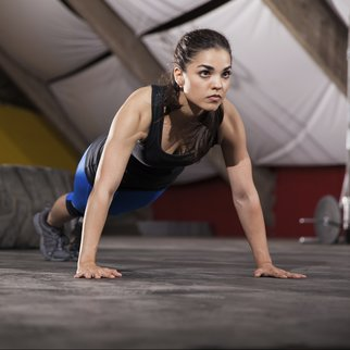 Gorgeous and strong brunette doing a set of push ups in a crossfit gym