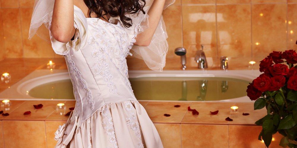 Woman in wedding dress relaxing into bath tube.