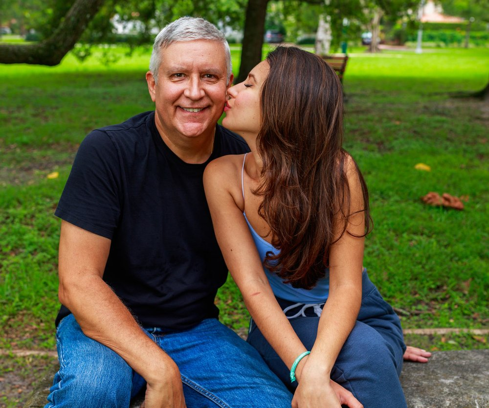 Father and daughter outdoor portrait in a park setting.