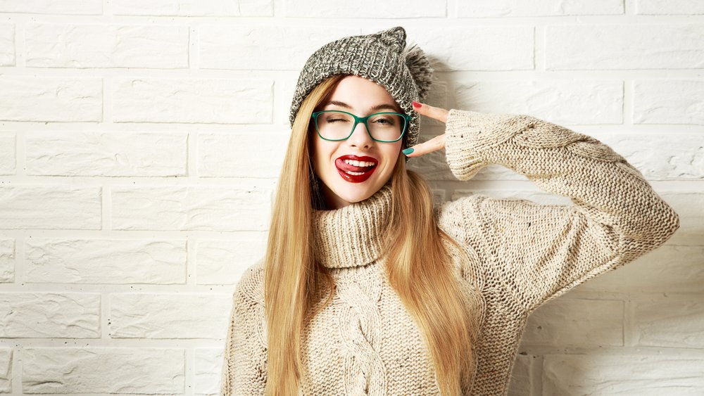 Funny Hipster Girl in Knitted Sweater and Beanie Hat Going Crazy at White Brick Wall Background. Trendy Casual Fashion Outfit in Winter. Toned Photo with Copy Space.