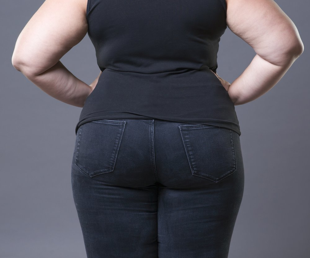 Fat female buttocks in black jeans, overweight woman body closeup on gray background