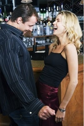 Mann und Frau schäkern an einer Bar