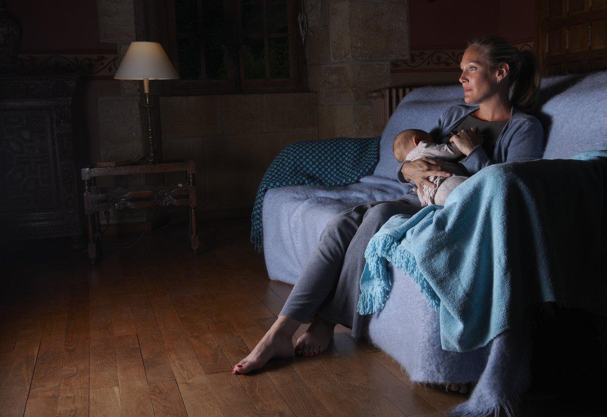 Frau stillt Baby im dunkeln