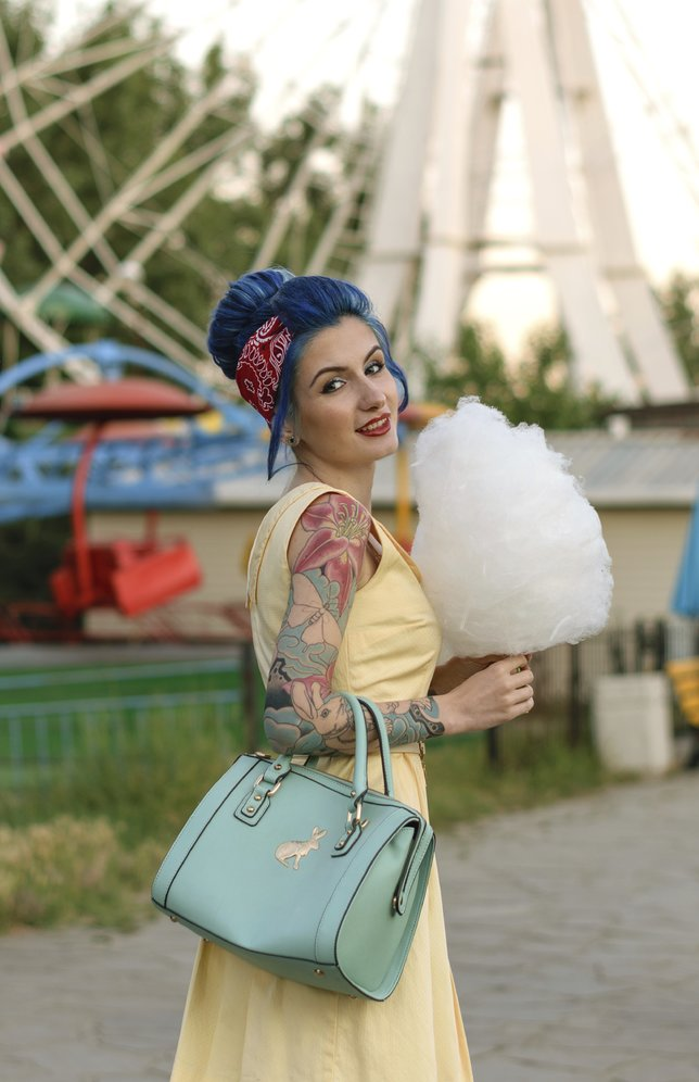 Girl with a tattoo with cotton candy in the hands of an amusement park on the background of traits kolesa.Retro style.