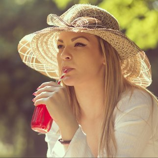 Portrait of a beautiful young woman, drinking juice on a sunny day in the park
