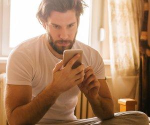 Mann sitzt auf Bett und schreibt am Handy